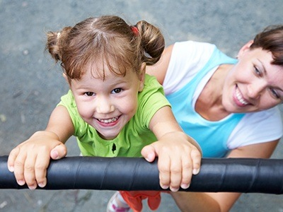 Mother and daughter at playground after emergency dental visit