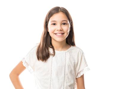 A young girl wearing a white blouse and showing off her cavity-free smile