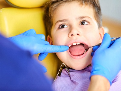 A dentist examines the oral cavity of a little boy seated in the dentist's chair