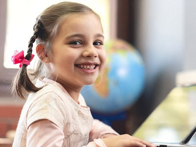 A little girl seated at a table preparing to do schoolwork while smiling
