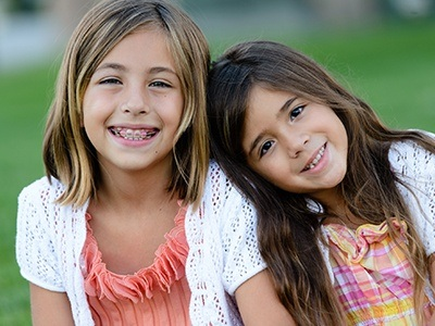 Two young girls smiling with interception orthodontics in place
