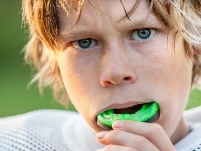 Teen placing green athletic mouthguard