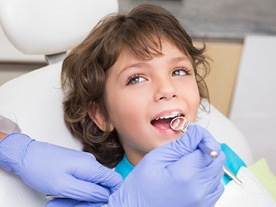 Dentist checking child's tooth colored filling