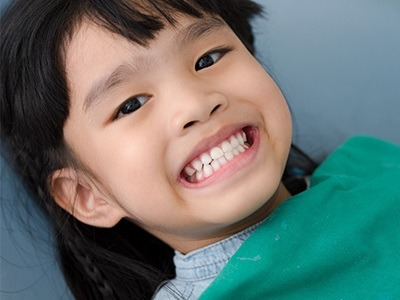 Child in dental chair smiling after metal free dental restoration placement