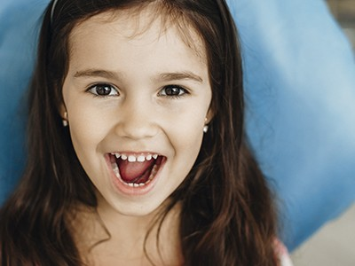 A young girl with long, dark hair smiling with her mouth open to show off her healthy teeth