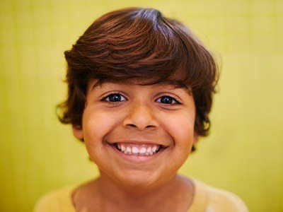 Child smiling with full set of primary teeth
