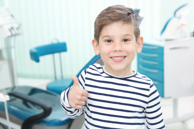a little boy wearing a striped shirt and giving a thumbs up after seeing his McKinney pediatric dentist