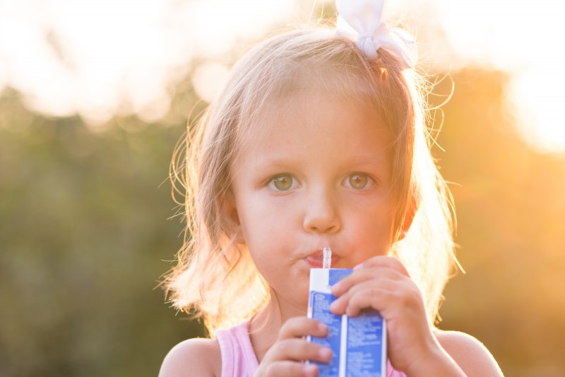 a little girl standing outside and drinking from a juice box